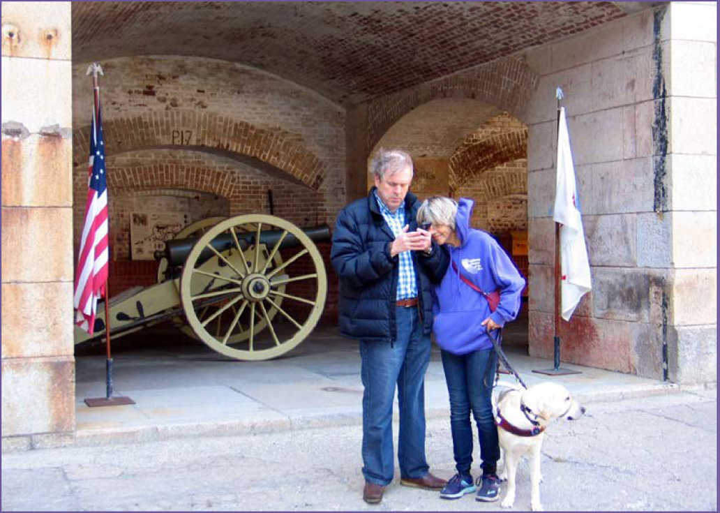California Council of the Blind members Susan and John Glass stand in front of a brick casement housing a civil war cannon as theyem listen to audio description of Fort Point on the UniD app.